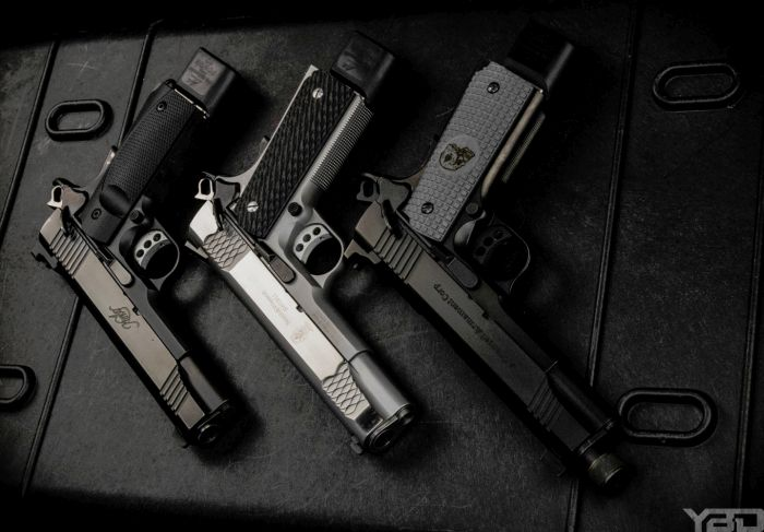 Three 1911s all lined up.  From left to right:  Kimber TLE II 1911, S&W E-Series 1911, and a Remington R1 Enhanced Advanced Armament Edition 1911.