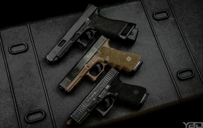 A custom Glock 34 Gen 3, Salient Arms International (SAI) Glock 17 Gen 3, and a custom Glock 19 Gen 4.
