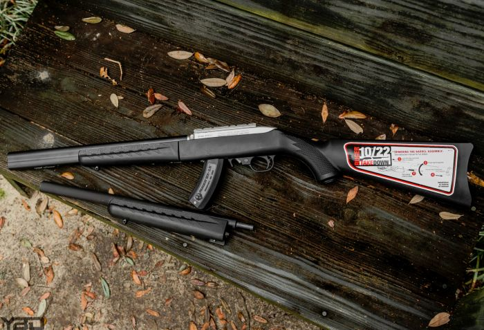A Ruger 10/22 Takedown with integrally suppressed barrel and a Gemtech MIST suppressor by its side.