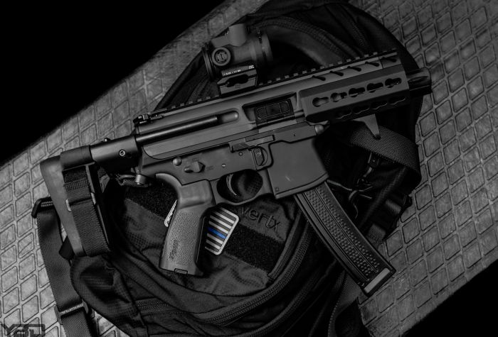 A Sig Sauer MPX with SB Tactical Brace with Trijicon MRO, and Vertx Commuter Sling Bag.