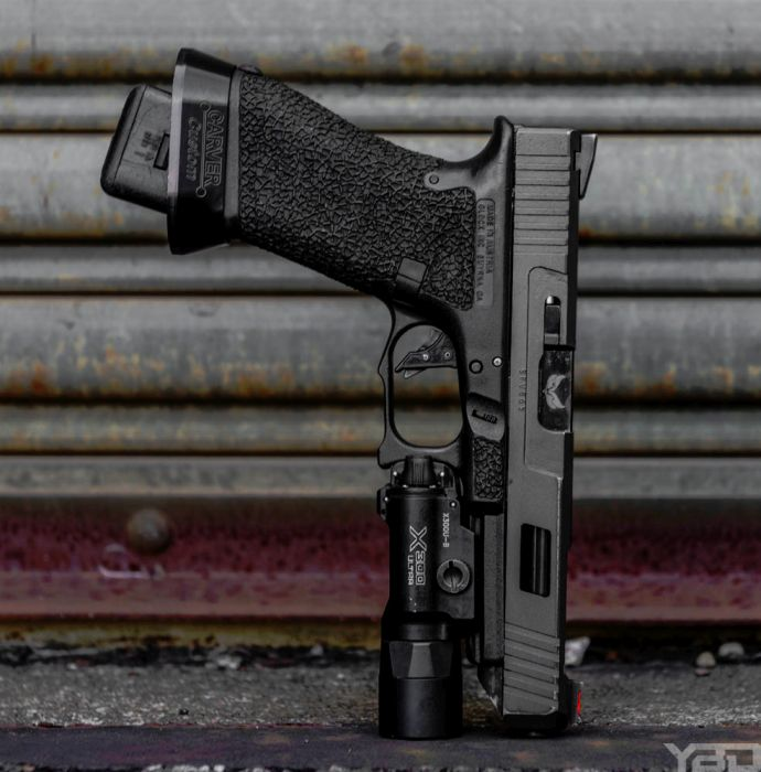 A close up of a custom Glock 34 Gen 3 with S3F Solutions Barrel, Overwatch Precision Barrel, and Carver Custom mag well with a Surefire X-300U-B on the end.