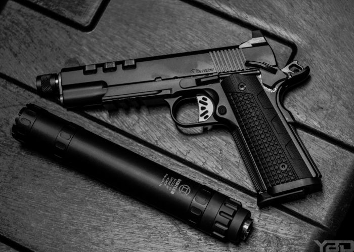 The Dan Wesson Discretion 1911 with a Gemtech LUNAR-45 suppressor by its side.