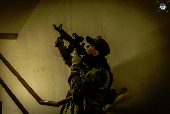 A student providing security on a stairway during one of our CQB classes.