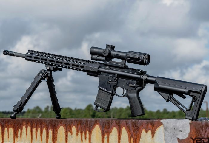 FNH FN-15 DMR II precision rifle with Trijicon VCOG optic and Accu-Tac bipod providing stability.