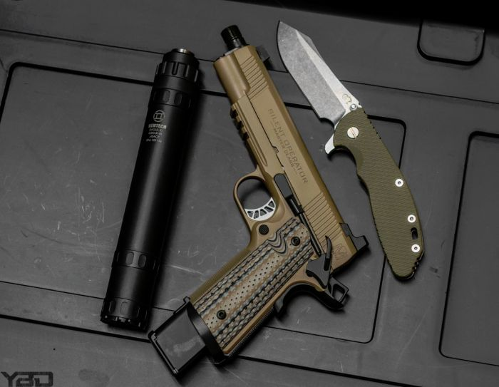 A Springfield Silent Operator 1911 with the Gemtech LUNAR-45 suppressed and a Rick Hinderer knife right by its side.