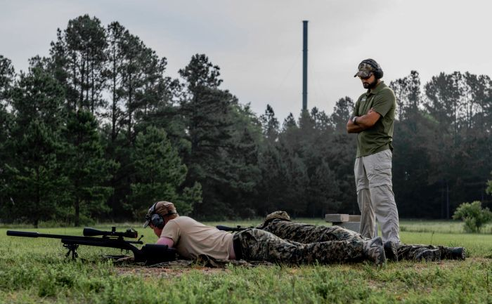 Tactical Instructor and Range Master Allen Ford watching his sniper students recording data in their sniper books.
