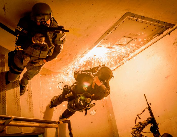 SWAT Operators pulling security while the breacher cuts through a door with the Broco Torch.